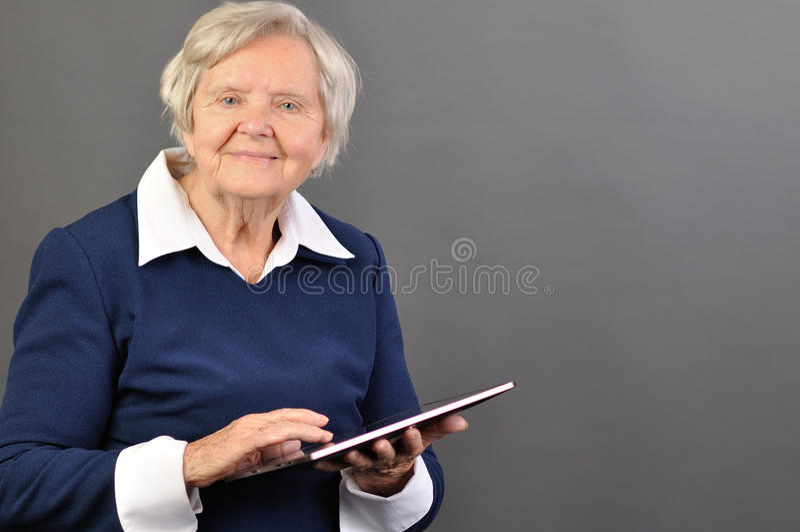 Femme heureuse supérieure avec la tablette. images stock