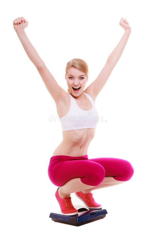 Femme heureuse sur l'échelle célébrant des weightloss image libre de droits