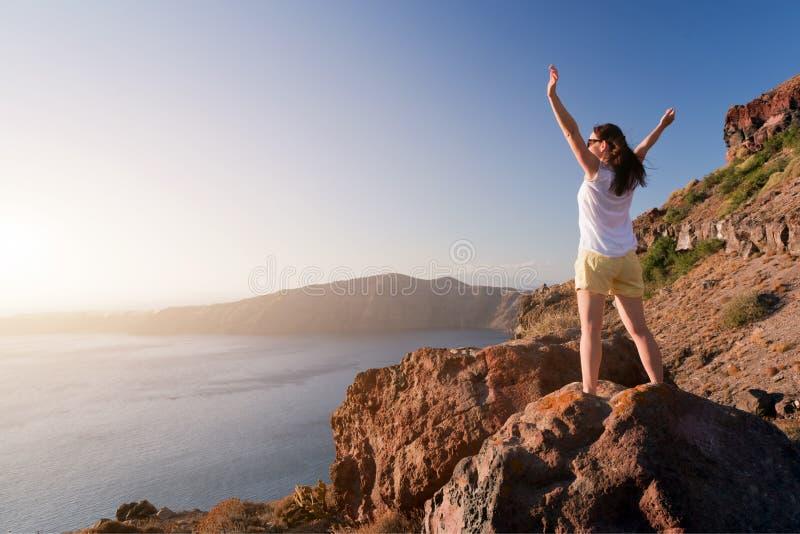 Femme heureuse sur la roche avec des mains  Santorini images libres de droits