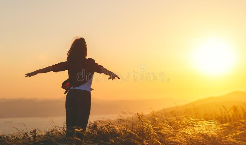 Femme heureuse sur le coucher du soleil dans des mains ouvertes d'iwith de nature images libres de droits