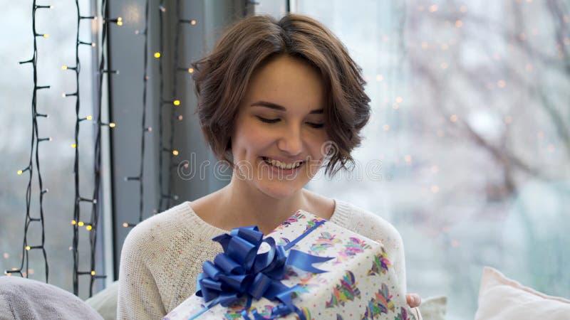Femme heureuse tenant des boîte-cadeau avec la décoration de Joyeux Noël à l'arrière-plan de fenêtre Fermez-vous de la femme tena images libres de droits