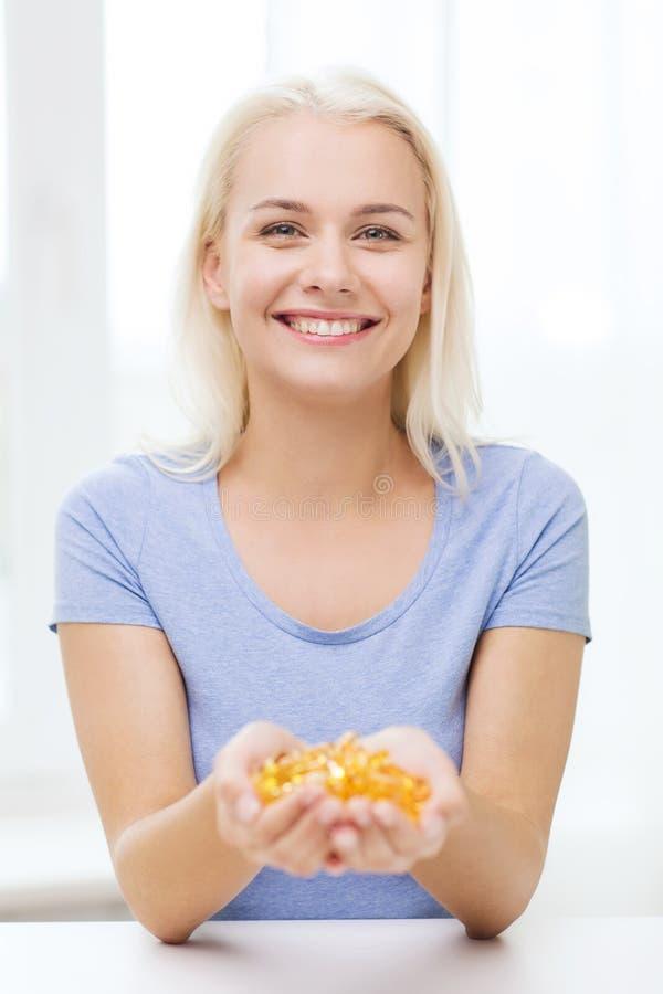 Femme heureuse tenant des capsules d'huile de poisson à la maison images stock