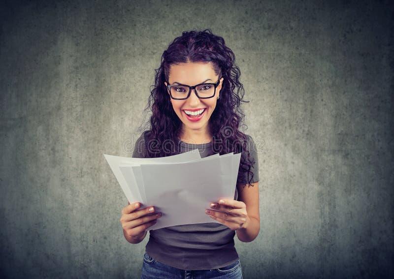 Femme heureuse tenant des papiers avec des résultats photographie stock