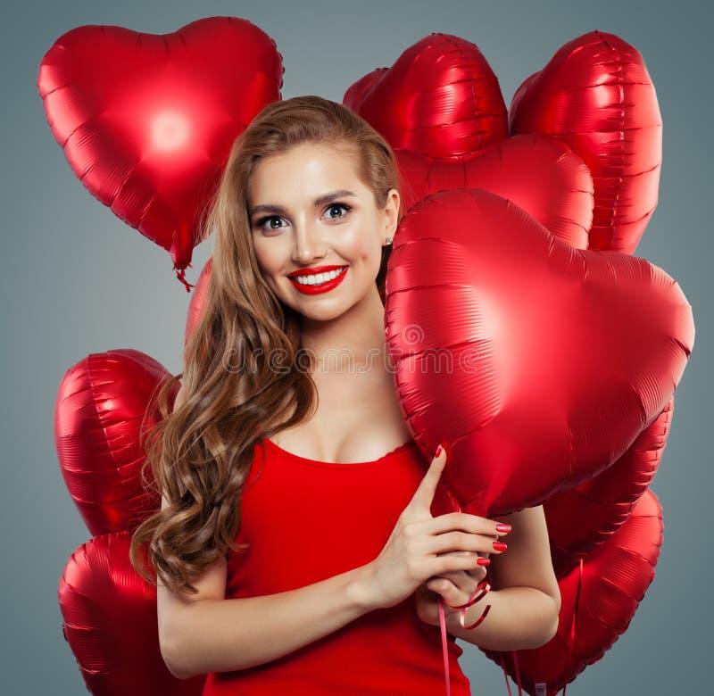 Femme heureuse tenant le coeur rouge de ballons Surprise, valentines les gens et concept de Saint-Valentin Maquillage rouge de lè photographie stock libre de droits