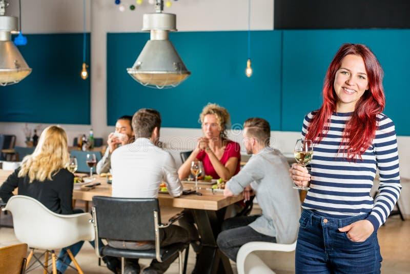 Femme heureuse tenant le verre à vin au restaurant images stock