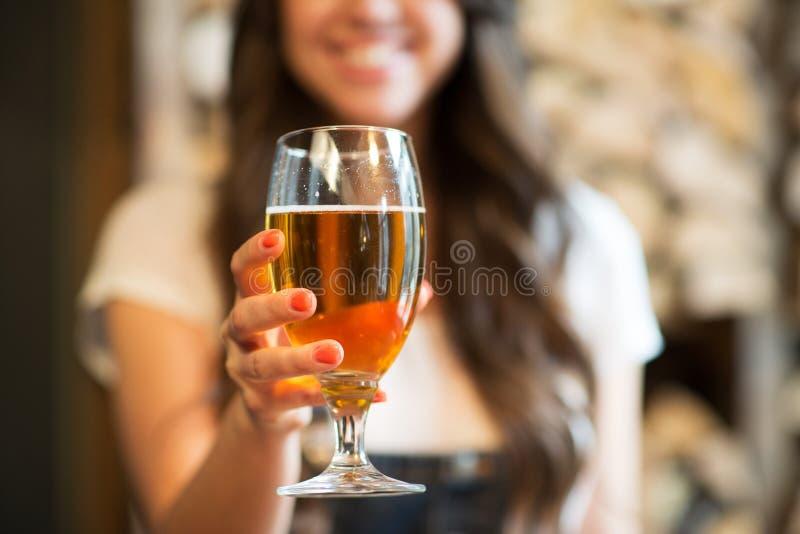 Femme heureuse tenant le verre de bière blonde d'ébauche images stock