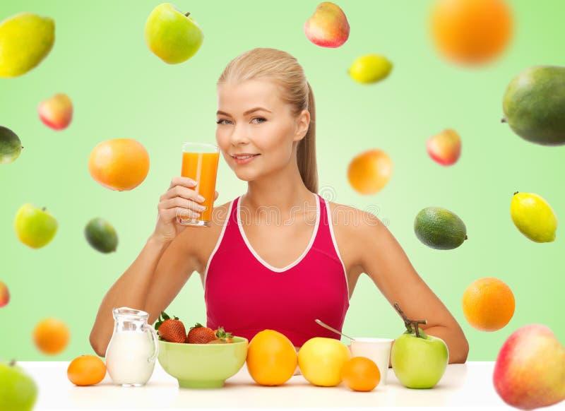 Femme heureuse tenant le verre de jus d'orange image stock