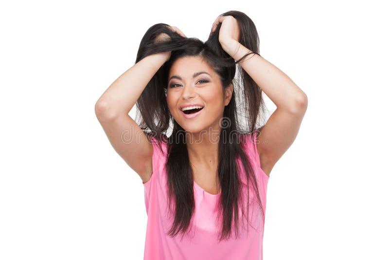 Femme heureuse tenant ses cheveux regardant l'appareil-photo. photos stock