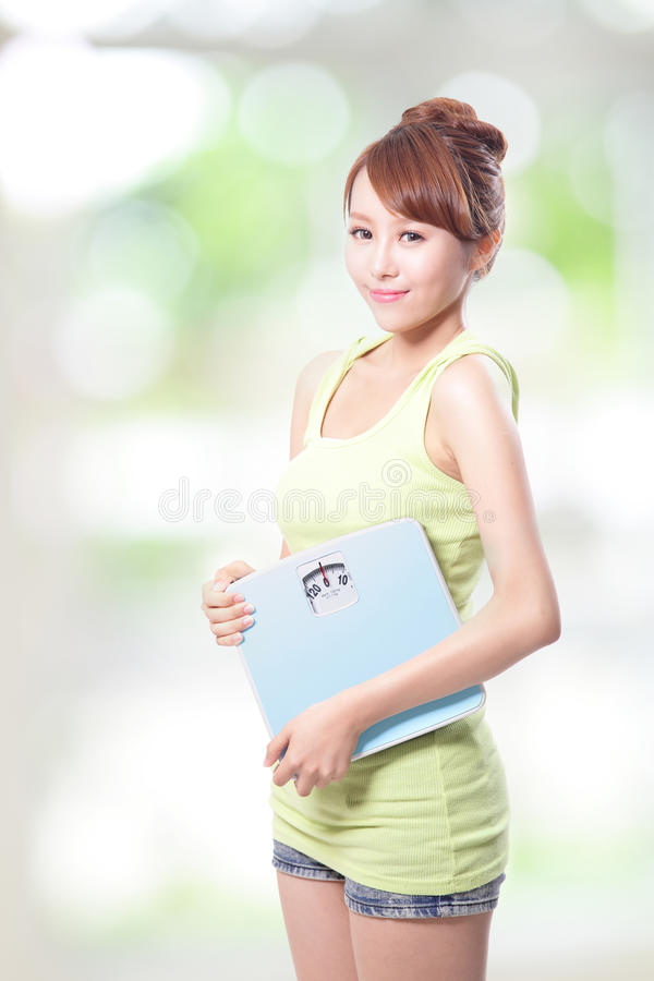 Femme heureuse tenant une échelle de poids photo stock