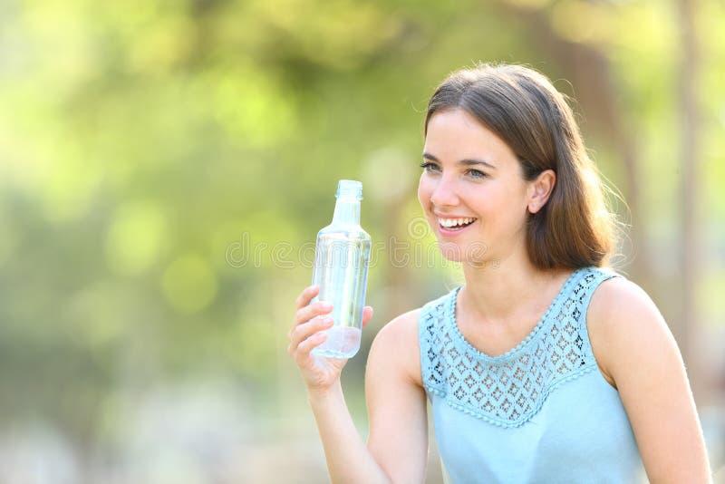 Femme heureuse tenant une bouteille d'eau en plastique sur le vert photo stock