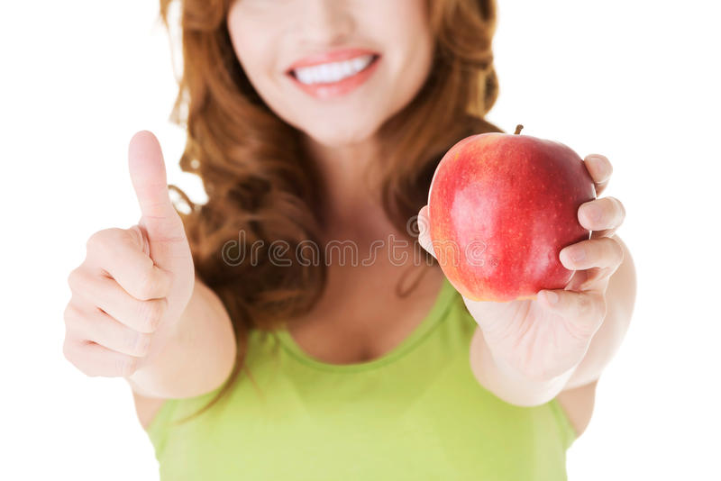 Femme heureuse tenant une pomme avec le pouce  images stock