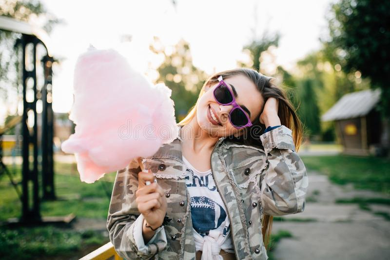 Femme heureuse tenant une sucrerie de coton, au parc image stock
