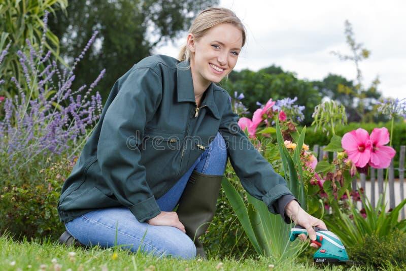 Femme heureuse travaillant dans le jardin d'arrière-cour de campagne photographie stock