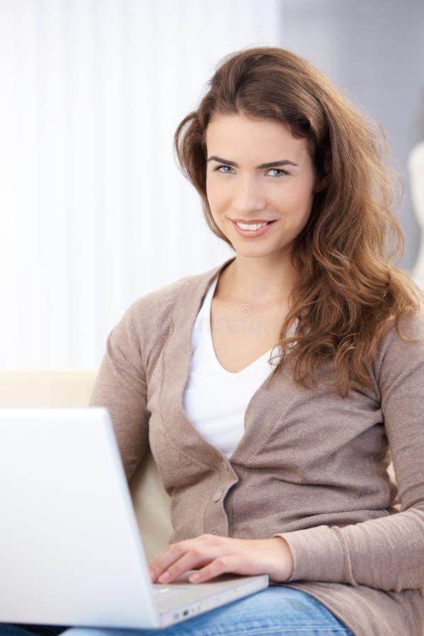 Femme heureux à l'aide de l'ordinateur portatif à la maison photo stock