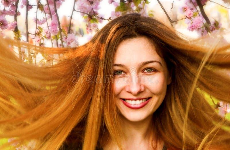 Femme heureux avec le beaux longs cheveu et fleurs photographie stock libre de droits