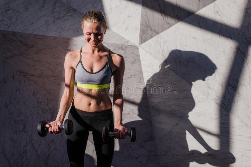 Femme heureux dans des haltères de fixation de vêtements de sport photos libres de droits