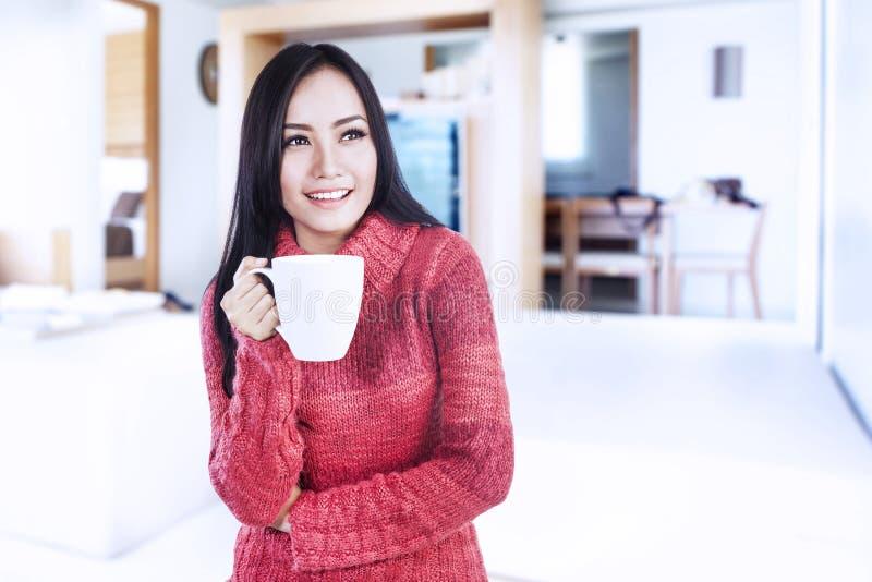 Femme heureux retenant le café chaud à la maison photos stock