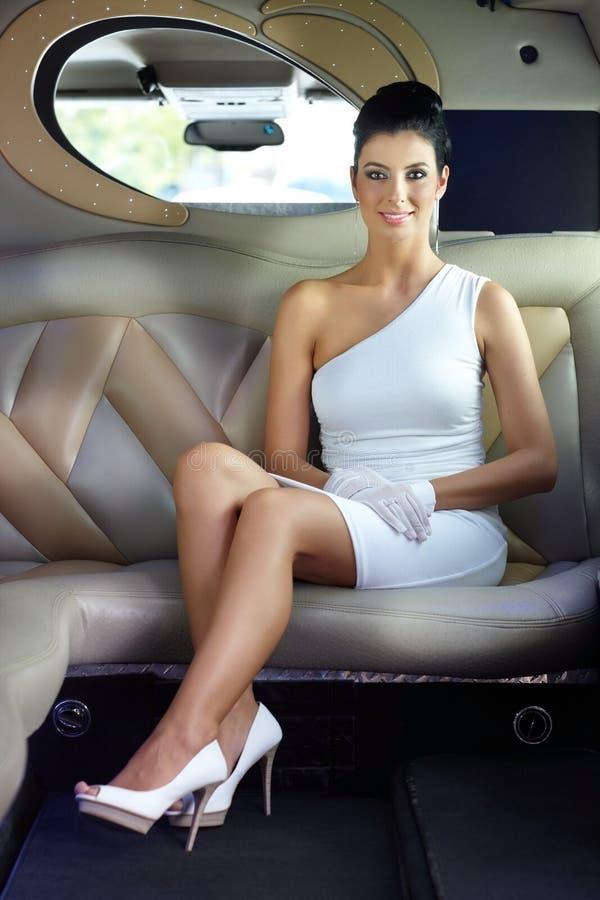 Femme heureux s'asseyant dans la limousine image libre de droits