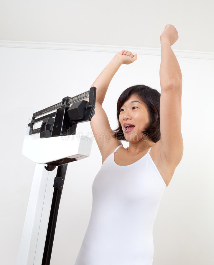 Femme heureux sur encourager d'échelle de poids photos stock