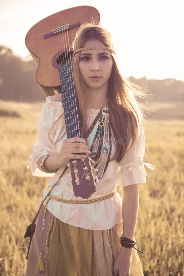 Download Femme Hippie Marchant Dans Le Domaine D'or Photo stock - Image du guitare, fille: 45365436