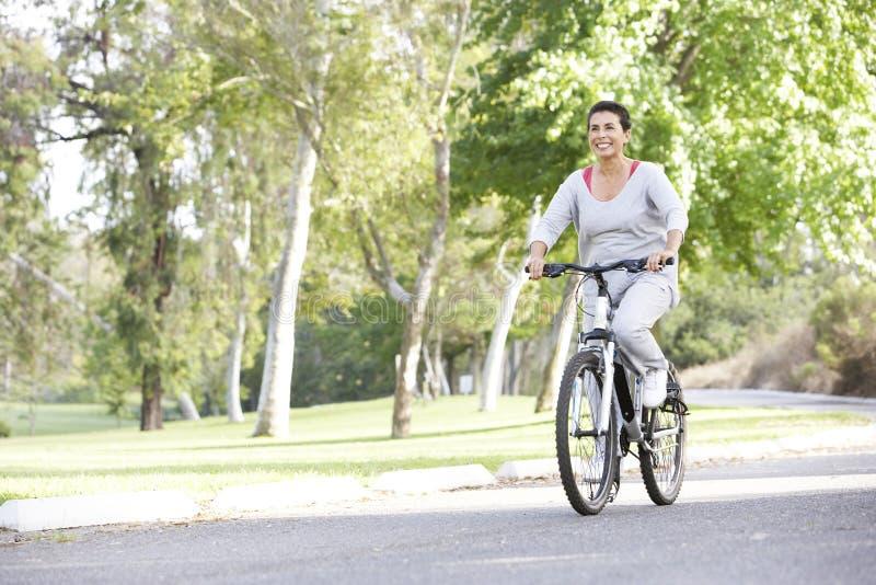 Femme hispanique aîné faisant un cycle en stationnement photographie stock libre de droits