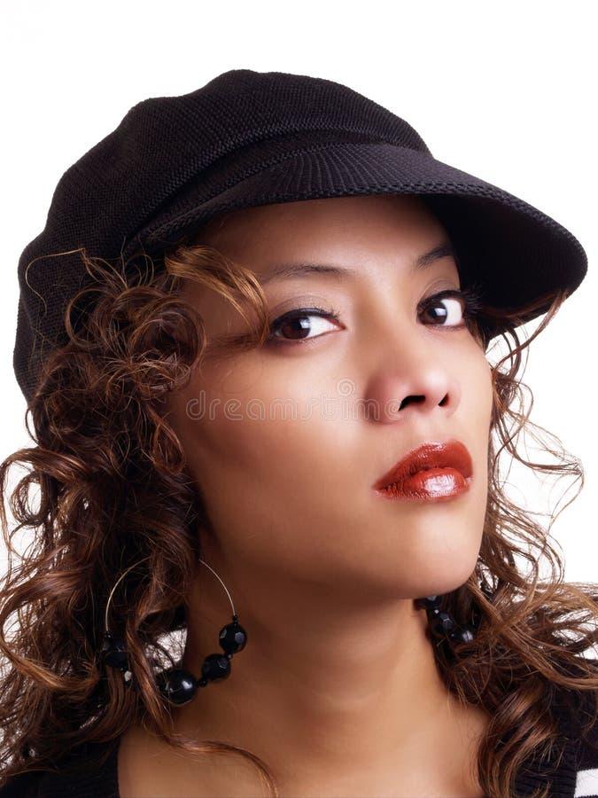 Femme hispanique assez jeune utilisant le chapeau noir photographie stock