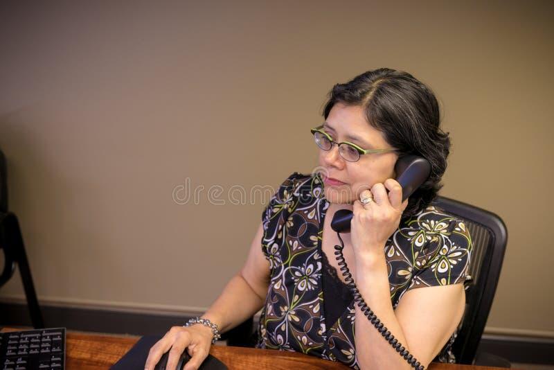 Femme hispanique au travail dans le bureau image stock