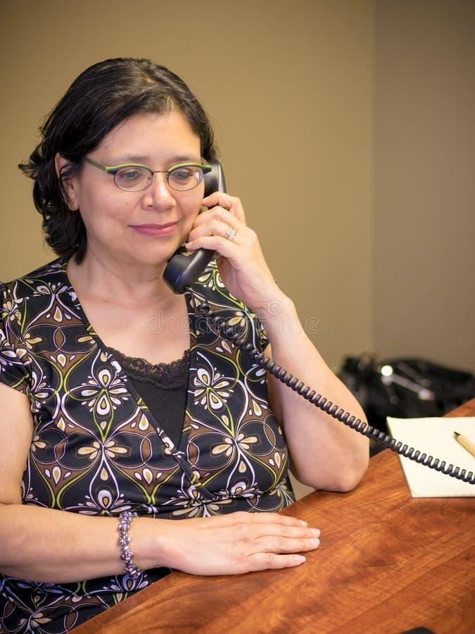 Femme hispanique au travail réalisant le travail de bureau photo stock