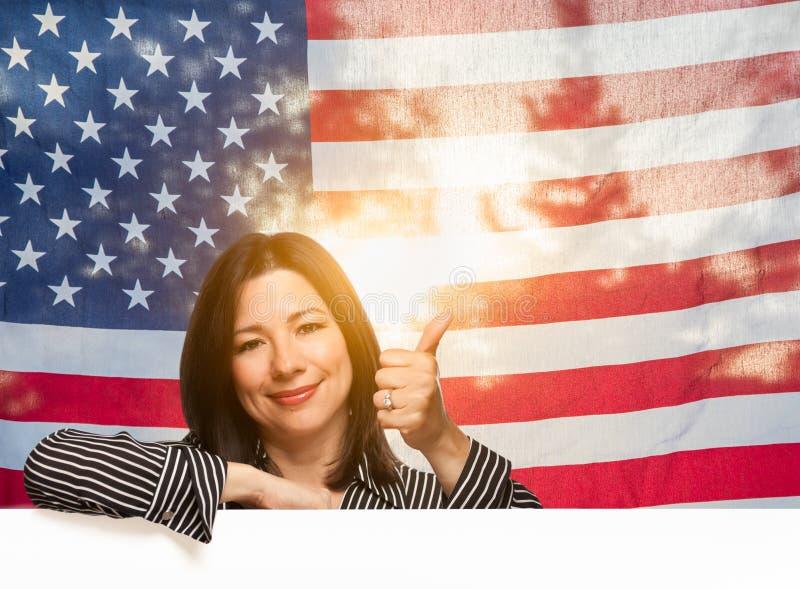 Femme hispanique avec des pouces devant le drapeau am?ricain image libre de droits