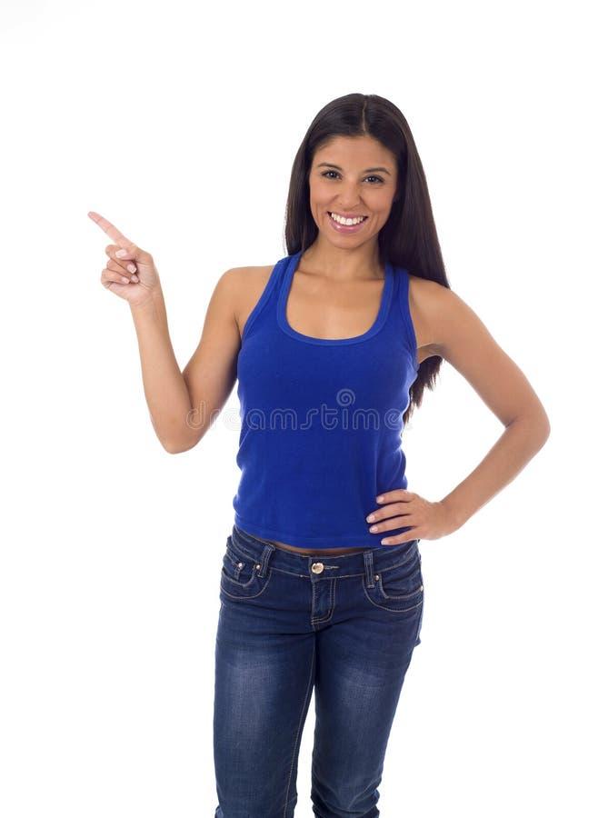 Femme hispanique dans le dessus occasionnel et jeans souriant pointage heureux et gai avec la présentation de doigt images stock