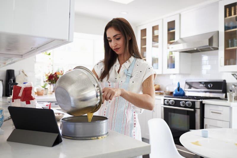 Femme hispanique millénaire faisant un gâteau dans sa cuisine, mélange de versement de gâteau dans une forme pour la cuisson photos stock