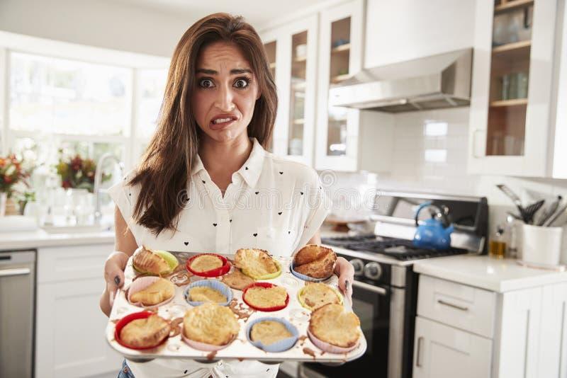 Femme hispanique millénaire présent ses gâteaux à la caméra après une catastrophe de cuisson, fin  images stock