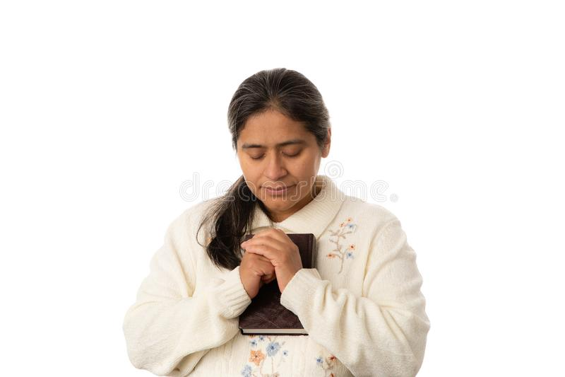 Femme hispanique priant tout en tenant la bible sur le fond blanc photo stock