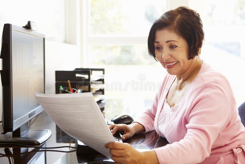 Femme hispanique supérieure travaillant sur l'ordinateur à la maison photo stock