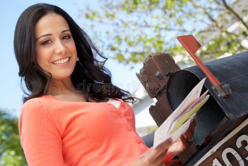 Femme hispanique vérifiant la boîte aux lettres photos libres de droits