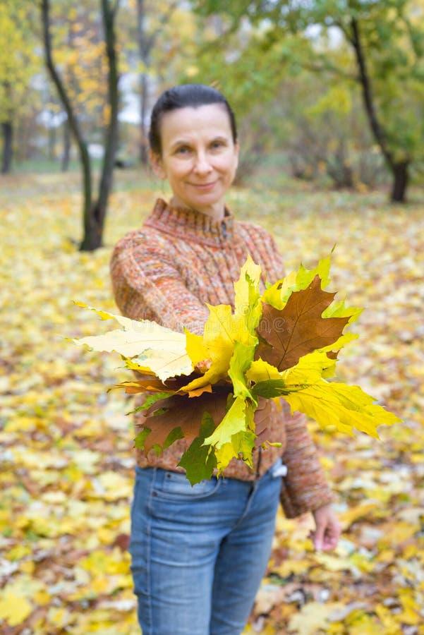 Femme Holdind et feuilles de représentation en automne image libre de droits