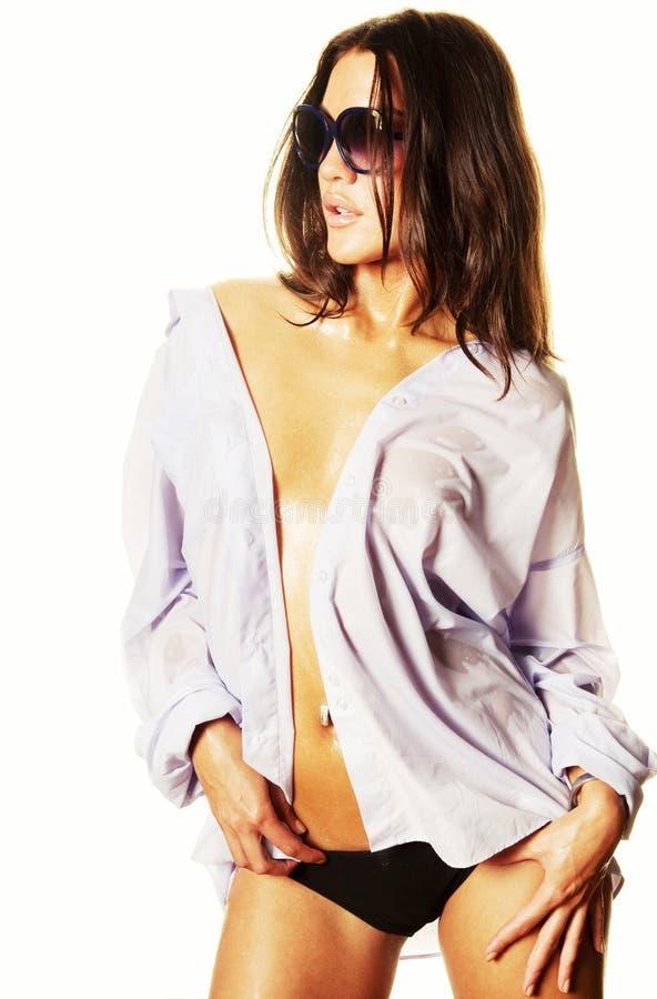 Femme humide dans la chemise et des lunettes de soleil blanches image stock