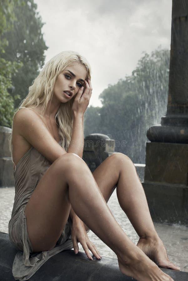 Femme humide sexy dans la fontaine de ville sous la pluie photos libres de droits