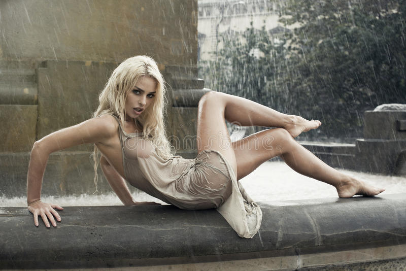 Femme humide sexy dans la fontaine de ville sous la pluie photographie stock