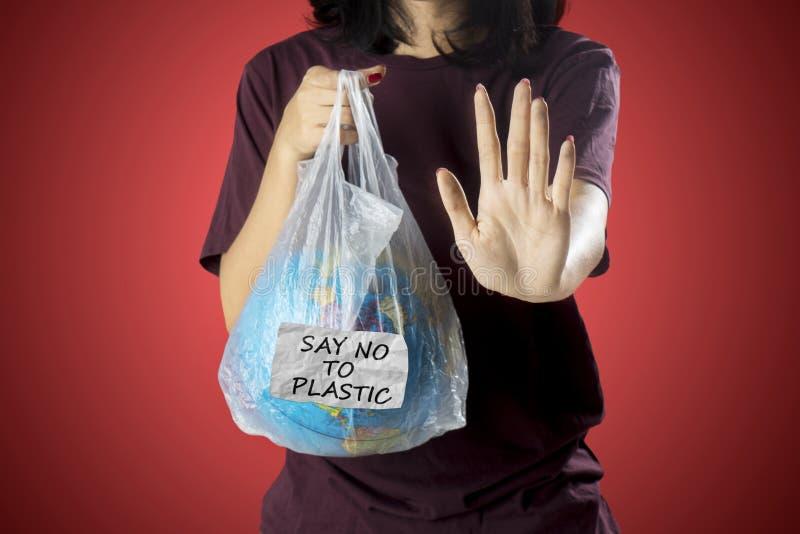 Femme inconnue faisant des gestes pour arrêter la pollution en plastique images stock