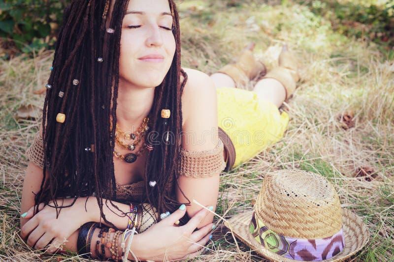 Femme indépendante décontractée et calme de style avec la coiffure de dreadlocks, se situant et se reposant dans l'herbe sèche, photo libre de droits