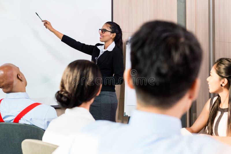 Femme indienne à la présentation d'affaires avec l'équipe photos stock