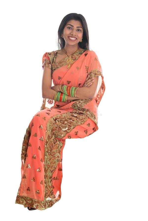 Femme indienne assise sur une chaise transparente. photographie stock libre de droits