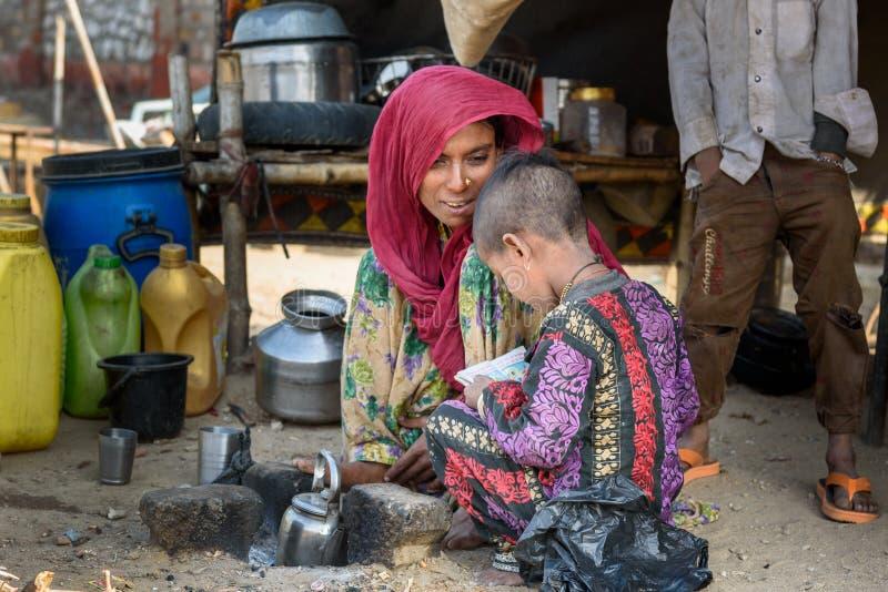 Femme indienne avec la fille s'asseyant sur la rue Les pauvres personnes viennent avec la famille à la ville du village pour le t photo libre de droits