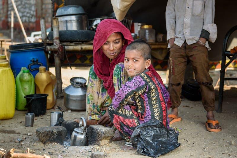 Femme indienne avec la fille s'asseyant sur la rue Les pauvres personnes viennent avec la famille à la ville du village pour le t photo stock