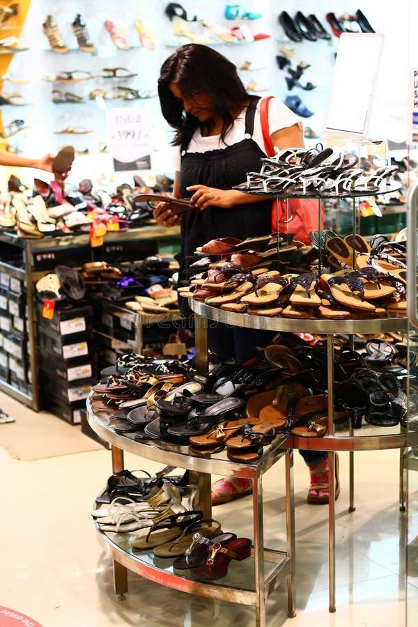 Femme indienne choisissant des chaussures dans un débouché pour les ventes au détail image libre de droits