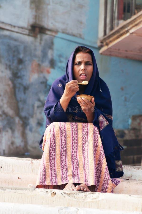 Femme indienne mangeant un repas sur le ghat près de la rivière sacrée le Gange à Varanasi photo stock