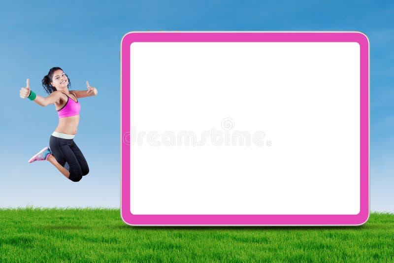 Femme indienne sautant près du panneau d'affichage au champ photo libre de droits