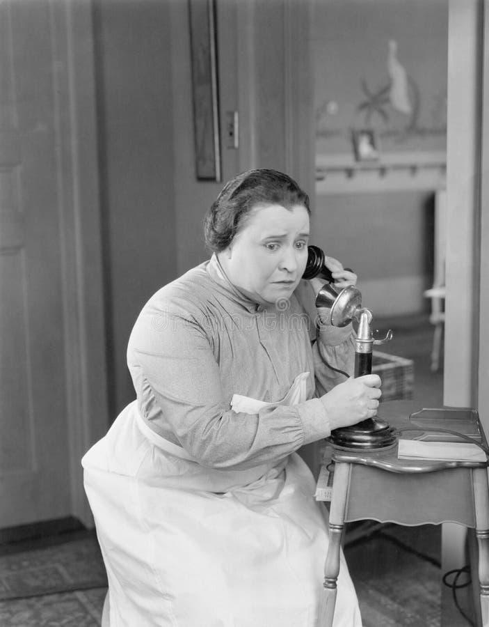 Femme inquiétée à l'aide du téléphone (toutes les personnes représentées ne sont pas plus long vivantes et aucun domaine n'existe image stock
