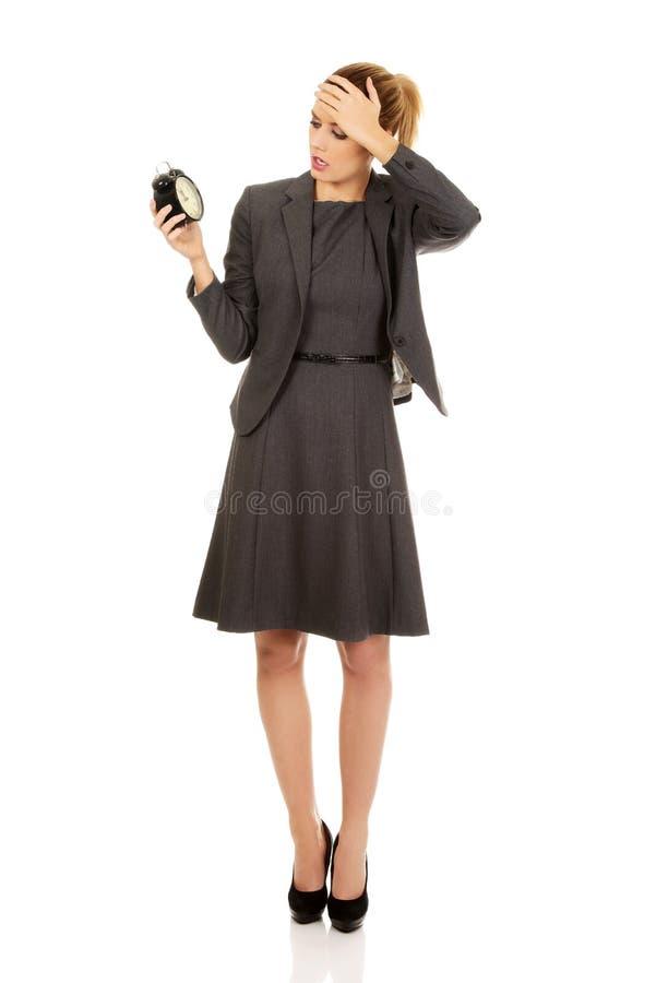 Femme inquiétée d'affaires tenant le réveil images stock